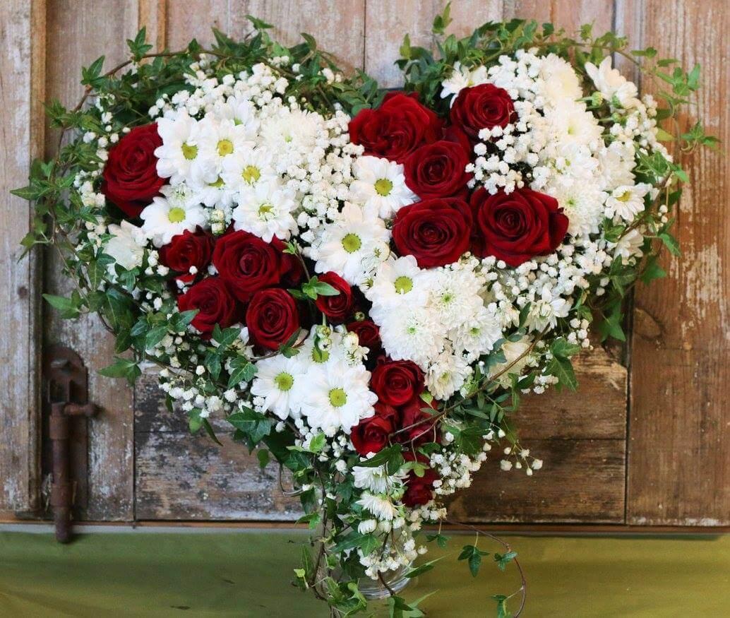Ett hjärta till begravning. Här har vi blandat blommor i vitt och rött. Blommorna varierar vi efter säsong. När man gör dessa hjärtan är det ofta vackert att låta floristen välja blommor och blanda sorter fritt.