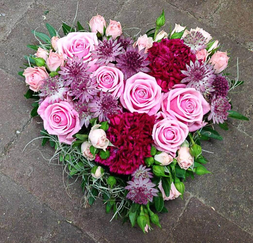 Ett litet hjärta till begravning. Här har vi blandat blommor i olika rosa nyanser. Blommorna varierar vi efter säsong. När man gör dessa hjärtan är det ofta vackert att låta floristen välja blommor och blanda sorter fritt.