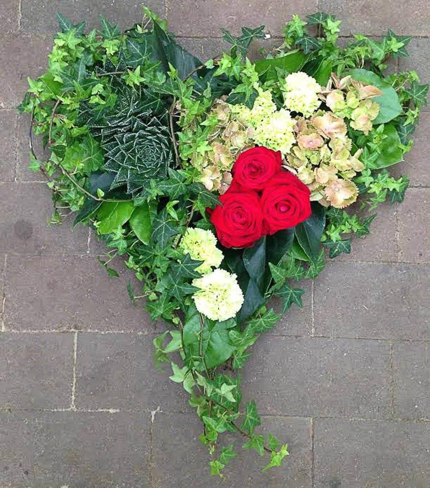 Ett hjärta till begravning. Här har vi fokuserat på det gröna och som accent har vi tre röda rosor. Materialet varierar vi efter säsong. När man gör dessa hjärtan är det ofta vackert att låta floristen välja blommor och blanda sorter fritt.