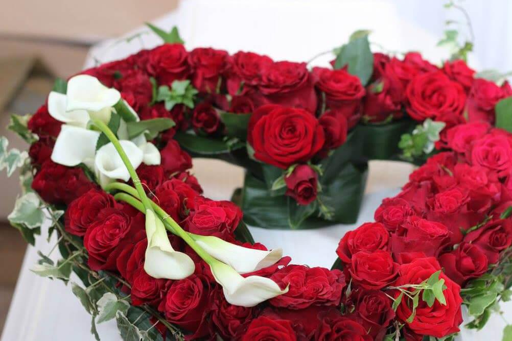 Öppet hjärta till begravning. Här har vi använt röda rosor och vita kallor. Blommorna kan variera efter säsong.