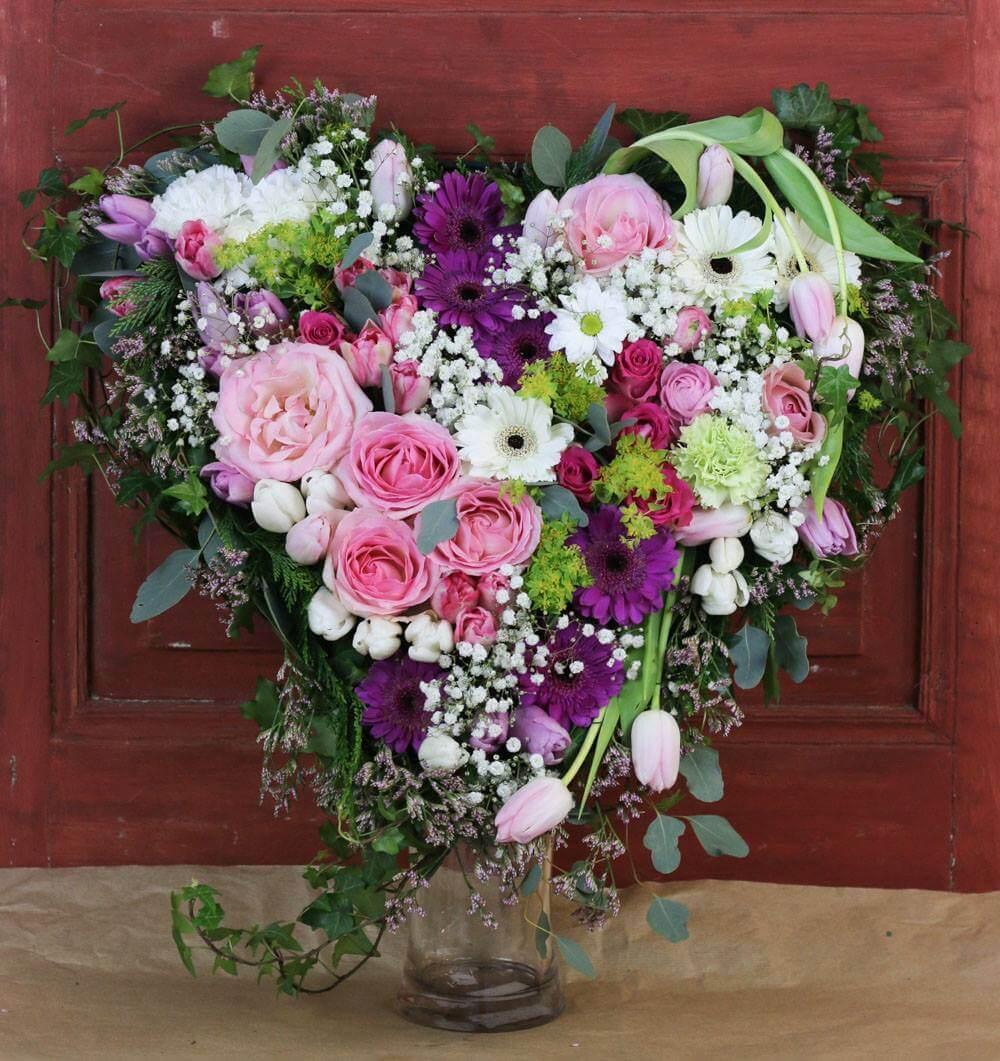 Ett hjärta till begravning. Här har vi blandat blommor i olika rosa, lila och vita nyanser. Blommorna varierar vi efter säsong. När man gör dessa hjärtan är det ofta vackert att låta floristen välja blommor och blanda sorter fritt.