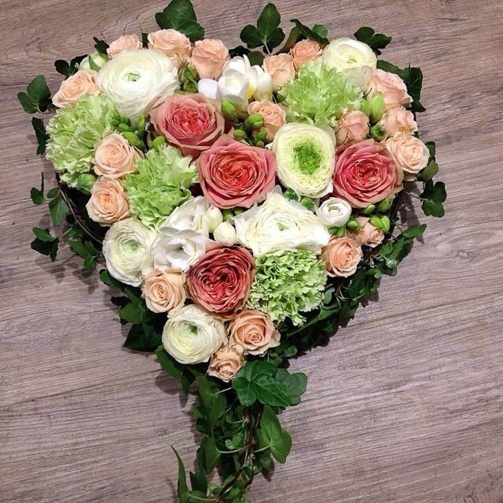 Ett hjärta till begravning. Här har vi blandat blommor i varmrosa, aprikos, lime och vitt. Blommorna varierar vi efter säsong. När man gör dessa hjärtan är det ofta vackert att låta floristen välja blommor och blanda sorter fritt.