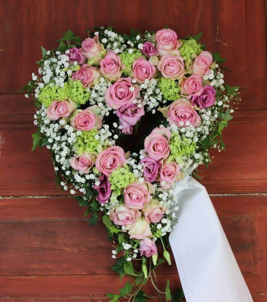 Ett öppet hjärta till begravning. Här har vi blandat blommor i rosa, lime och vitt. Blommorna varierar vi efter säsong. När man gör dessa hjärtan är det ofta vackert att låta floristen välja blommor och blanda sorter fritt.