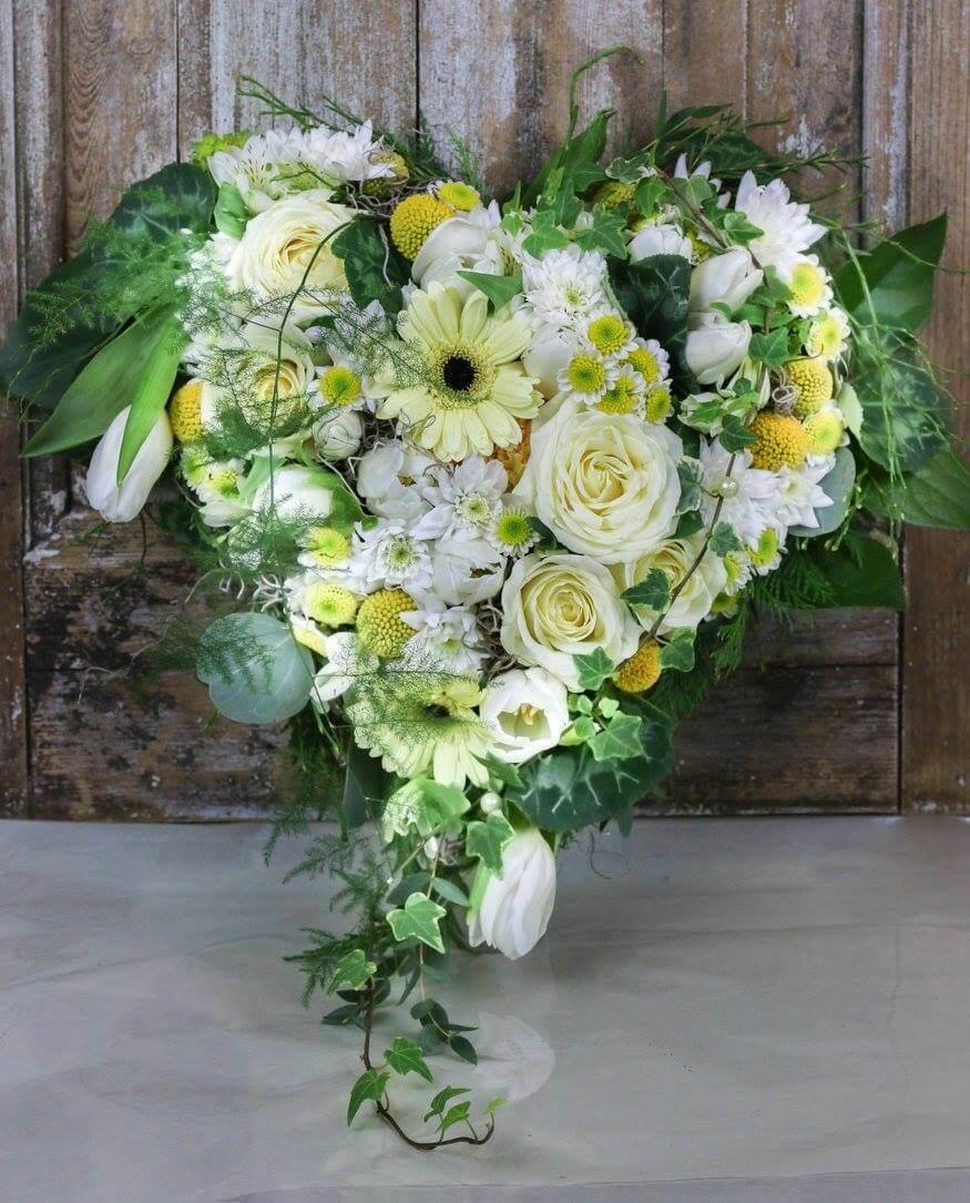 Ett hjärta till begravning. Här har vi blandat blommor i vitt, creme och gult. Blommorna varierar vi efter säsong. När man gör dessa hjärtan är det ofta vackert att låta floristen välja blommor och blanda sorter fritt.