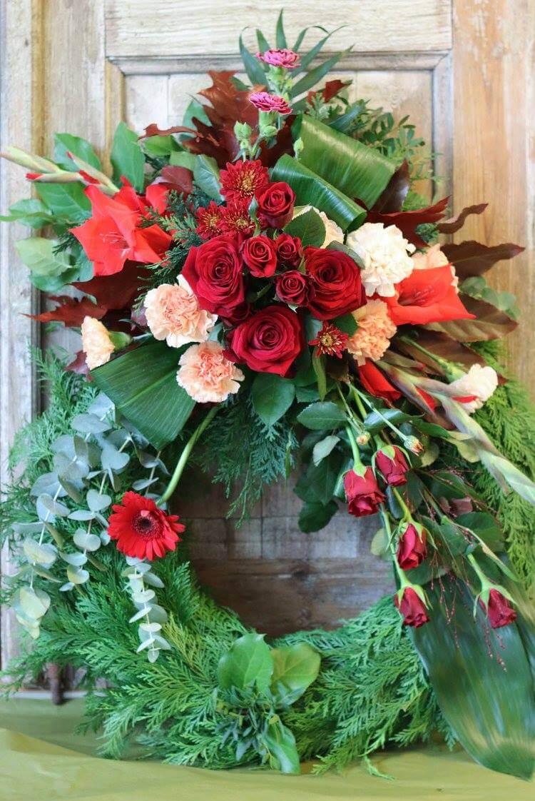 Klassisk begravningskrans med dekoration på stomme klädd med cypress. Blomvalet varierar men just här har vi använt blommor i varma toner som rött och aprikos. Det är rosor, nejlikor, eukalyptus mm.