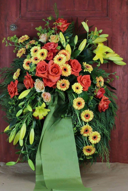 Klassisk begravningskrans med dekoration på stomme klädd med cypress. Blomvalet varierar men just här har vi använt blommor i gult och orange. Det är rosor, germini och liljor.