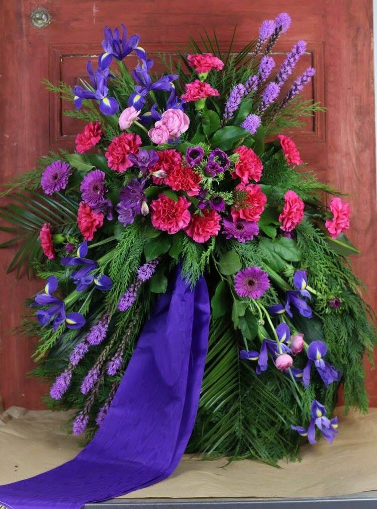 Klassisk begravningskrans med dekoration på stomme klädd med cypress. Blomvalet varierar men just här har vi använt blommor i cerise, lila och blått. Det är nejlikor, liatris, germini, iris och anemoner.