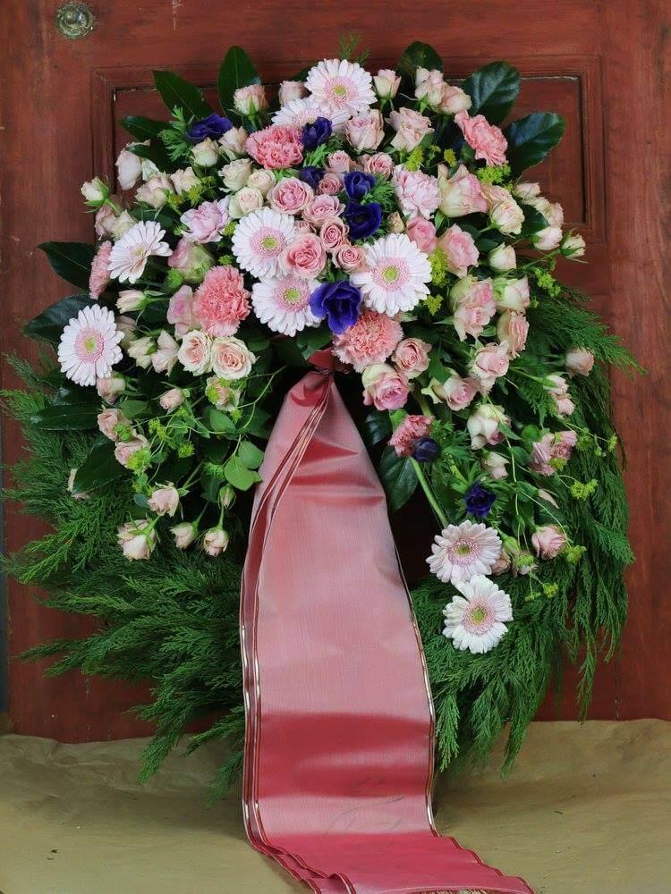 Klassisk begravningskrans med dekoration på stomme klädd med cypress. Blomvalet varierar men just här är det en dominans av rosa germini och rosor med ett inslag av blå anemon.