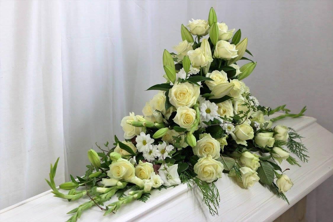 En kistdekoration helt i vitt. Blommorna kan variera efter säsong, men just här har vi använt rosor, liljor, gladiolus, krysantemum samt vackert grönt.