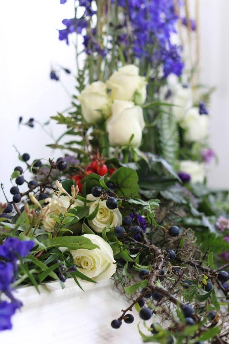 Med inspiration från havet skapade vi en kistdekoration i vitt och blått. Den starkt blå färgen på riddarsporrarna är dominerande. Följt av vita rosor och diverse naturmaterial och fiskenät bildar det en vacker helhet. Blommorna kan variera efter säsong.