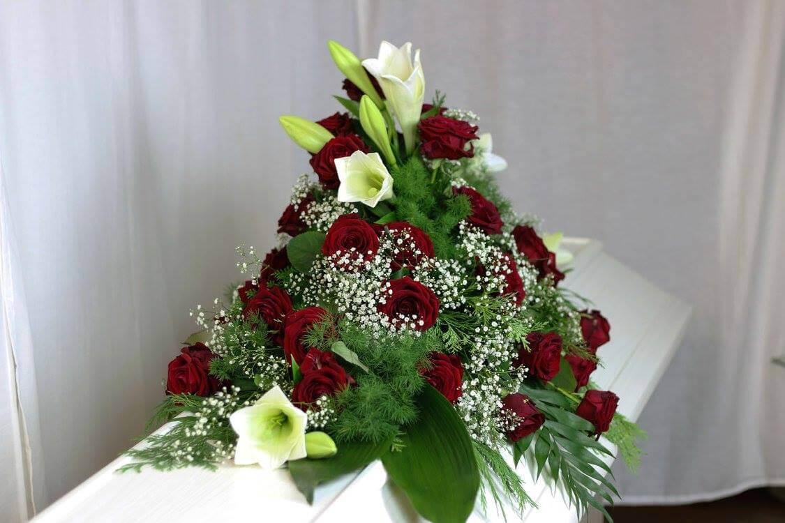 En kistdekoration på klassiskt vis. Röda rosor, vita liljor, brudslöja och vackert grönt. Blommorna kan variera efter säsong.