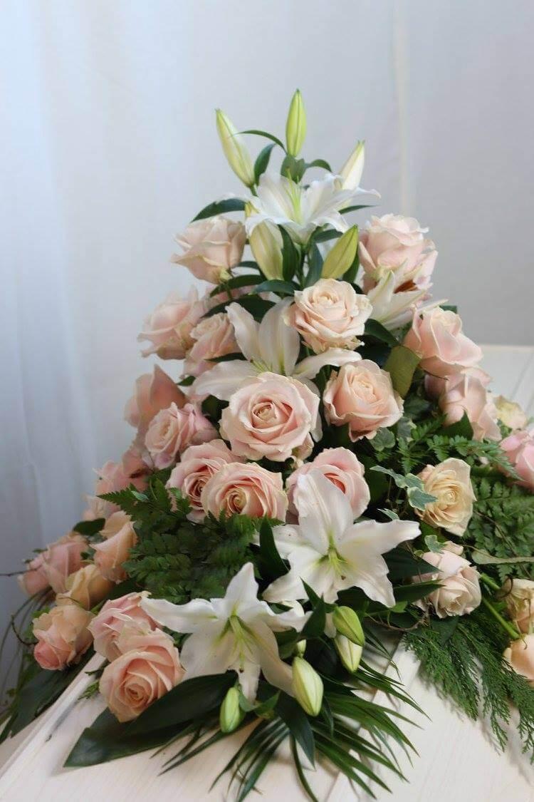 En pampig kistdekoration i vitt och ljusrosa. Blekt rosa rosor, vita liljor och vackert grönt bildar en fin helhet. Blommorna kan variera efter säsong.