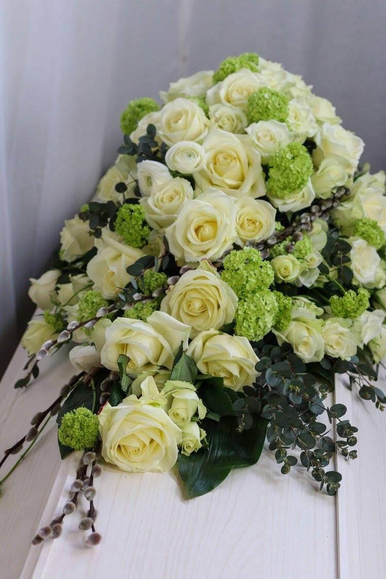 En pampig kistdekoration i vitt och lime. Vita rosor, olvon och vackert grönt bildar en fin helhet. Blommorna kan variera efter säsong.