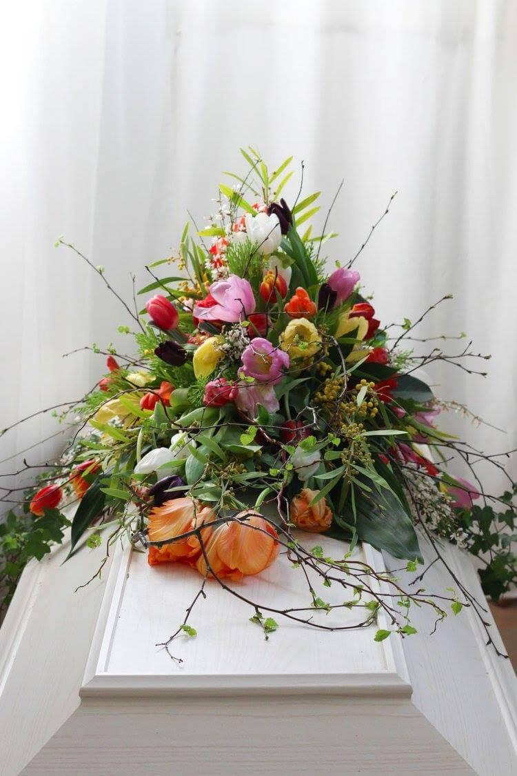 En vårig kistdekoration med tulpaner, björkris mm. Blommorna kan variera efter säsong. Tänk på att dessa blommor inte finns hela året.