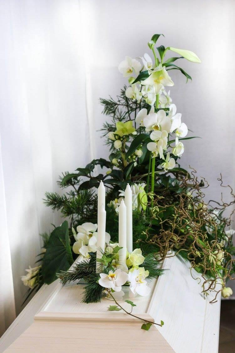 En tvådelad kistdekoration med ljus, vita orkidéer och liljor samt mycket naturmaterial. Blommorna kan variera efter säsong.