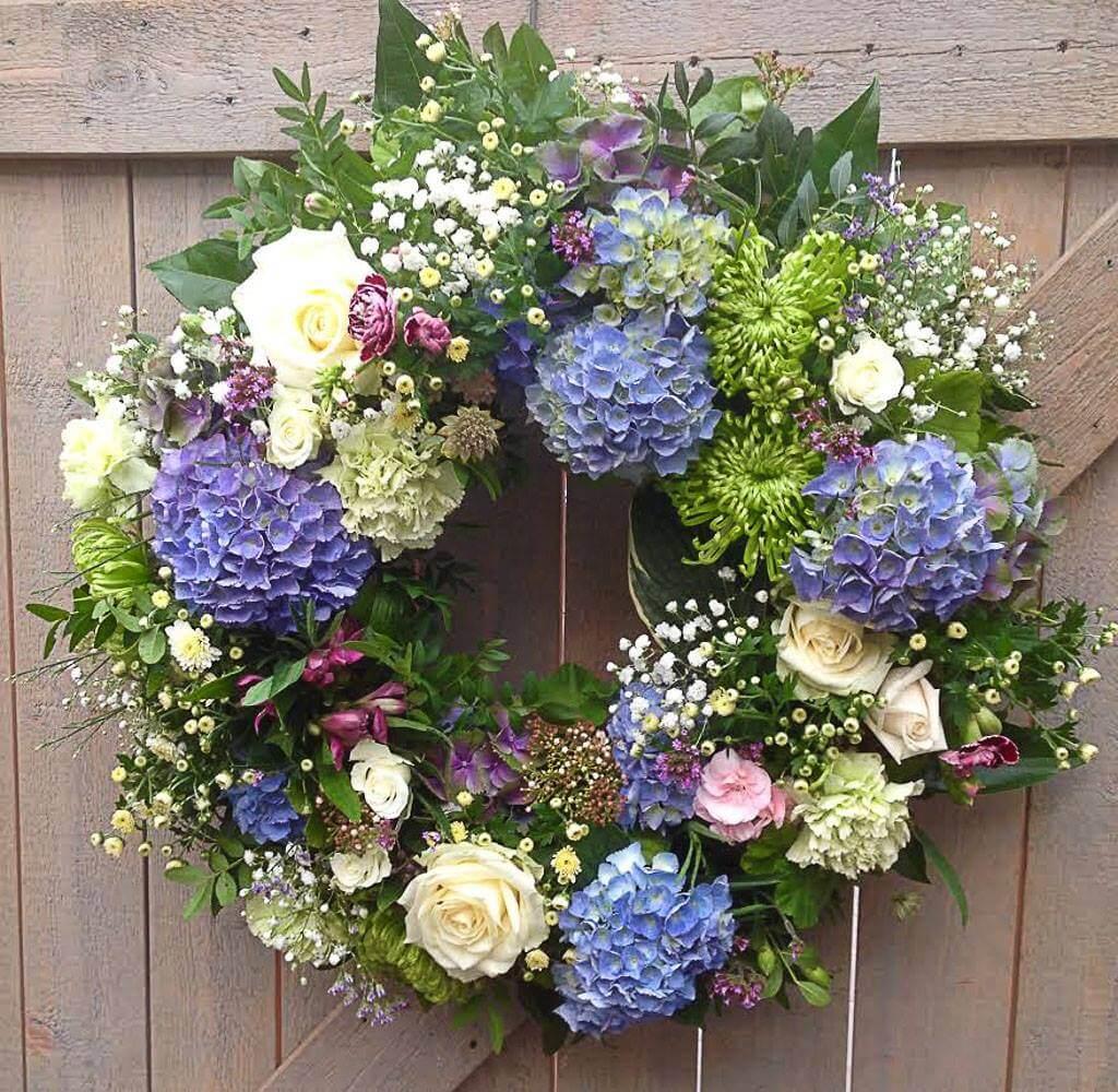 Rundbunden begravningskrans i blått, lime och vitt. Blommorna varierar vi efter säsong. När man gör dessa kransar är det ofta vackert att låta floristen välja blommor och blanda sorter fritt.