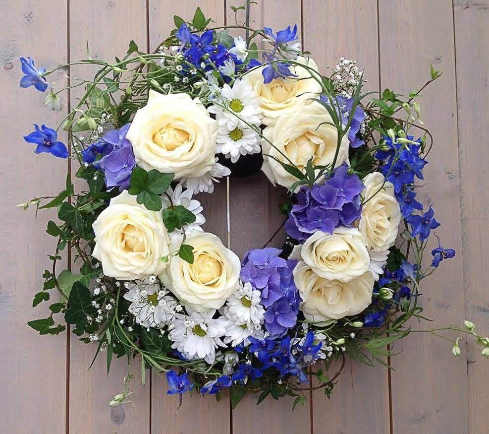 Rundbunden begravningskrans i blått, vitt och vackert grönt. Blommorna varierar vi efter säsong. När man gör dessa kransar är det ofta vackert att låta floristen välja blommor och blanda sorter fritt.