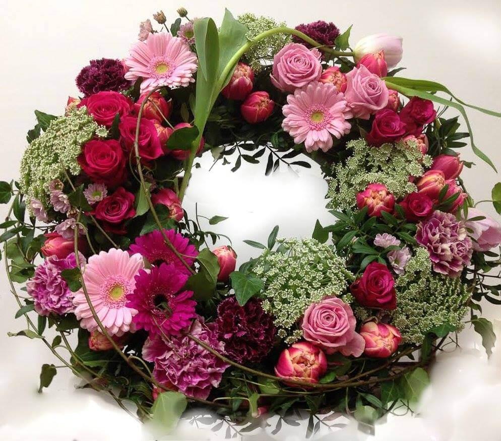 Rundbunden begravningskrans i rosa, vitt och vackert grönt. Blommorna varierar vi efter säsong. När man gör dessa kransar är det ofta vackert att låta floristen välja blommor och blanda sorter fritt.