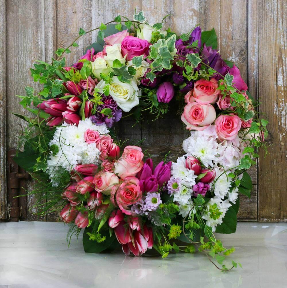 Rundbunden begravningskrans i rosa, vitt, lila och vackert grönt. Blommorna varierar vi efter säsong. När man gör dessa kransar är det ofta vackert att låta floristen välja blommor och blanda sorter fritt.