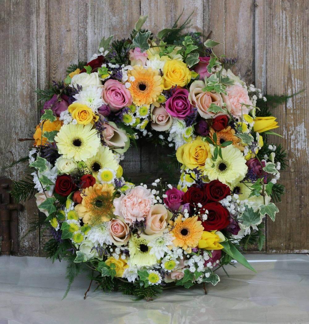 Rundbunden begravningskrans i blandade färger med betoning på pastell. Blommorna varierar vi efter säsong. När man gör dessa kransar är det ofta vackert att låta floristen välja blommor och blanda sorter fritt.