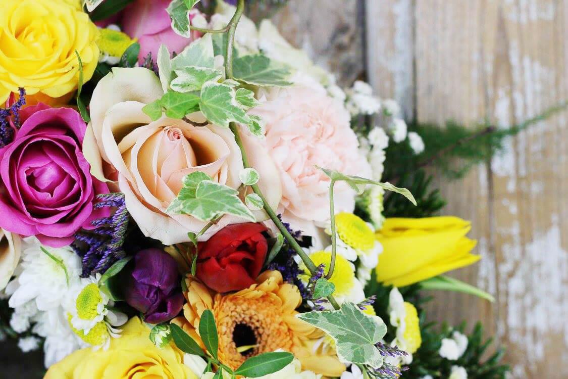 Närbild på en av våra begravningskransar. Blandade blommor, till exempel rosor, tulpaner, germini och nejlika.