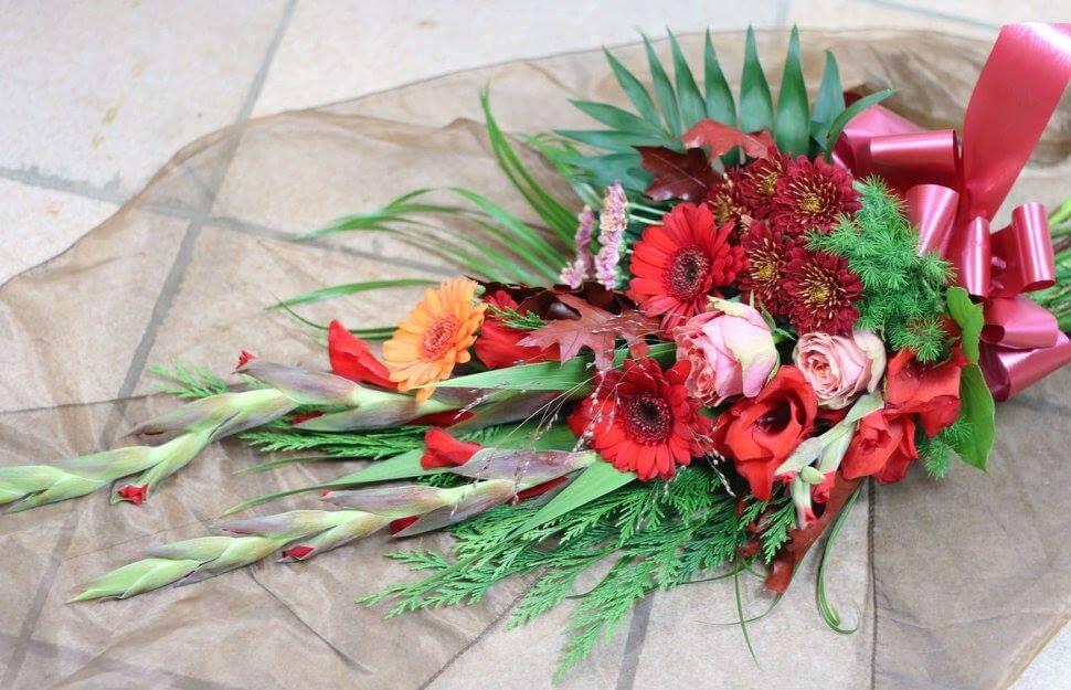 En sorgbukett i varma färger. Blomsorterna kan variera, men just här har vi använt rosor, germini, krysantemum, gladiolus och vackra gröna blad.