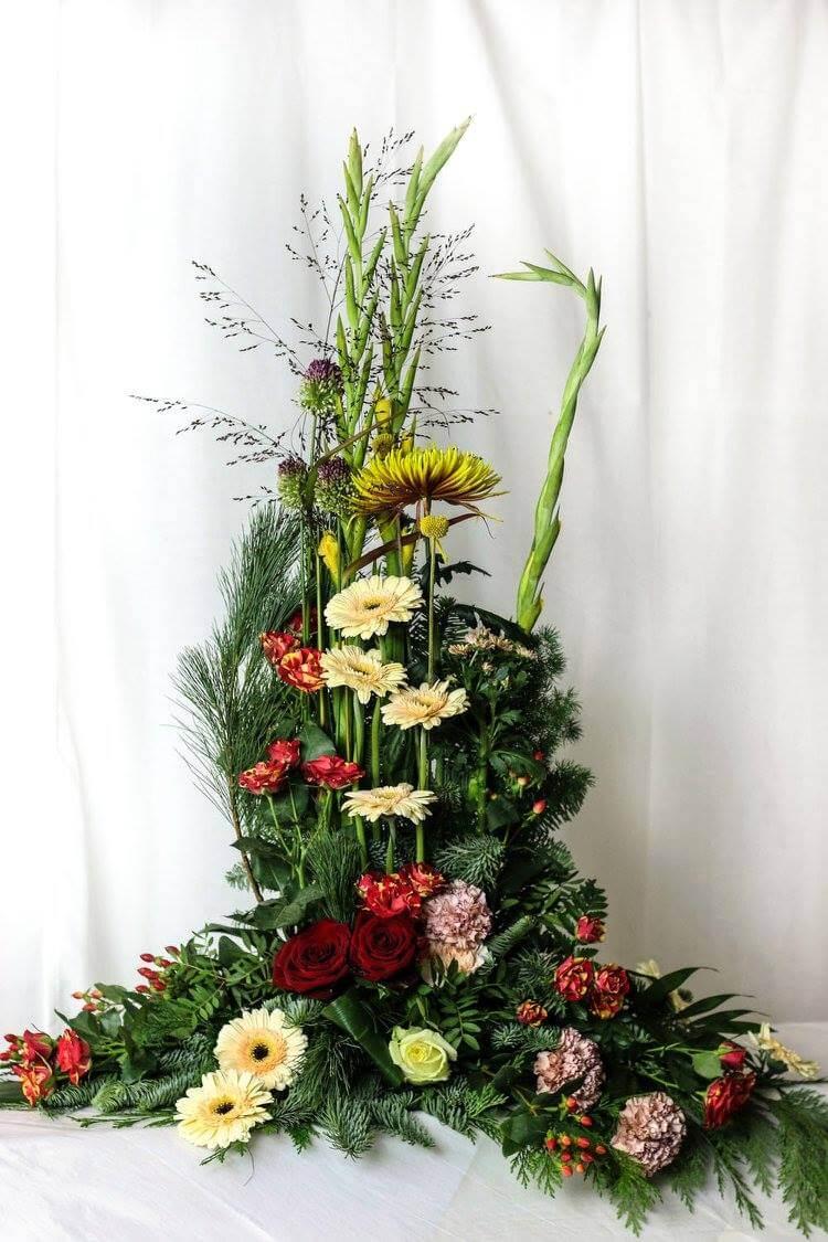 Hög sorgdekoration i blandade färger. Blomvalet varierar efter säsong men just här har vi använt gladiolus, germini, rosor, nejlikor mm.