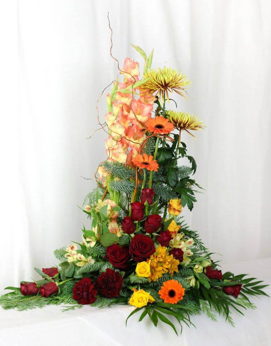 Hög sorgdekoration i varma nyanser i rött, orange och gult. Blomvalet varierar efter säsong men just här har vi använt gladiolus, germini, rosor och alstroemeria.