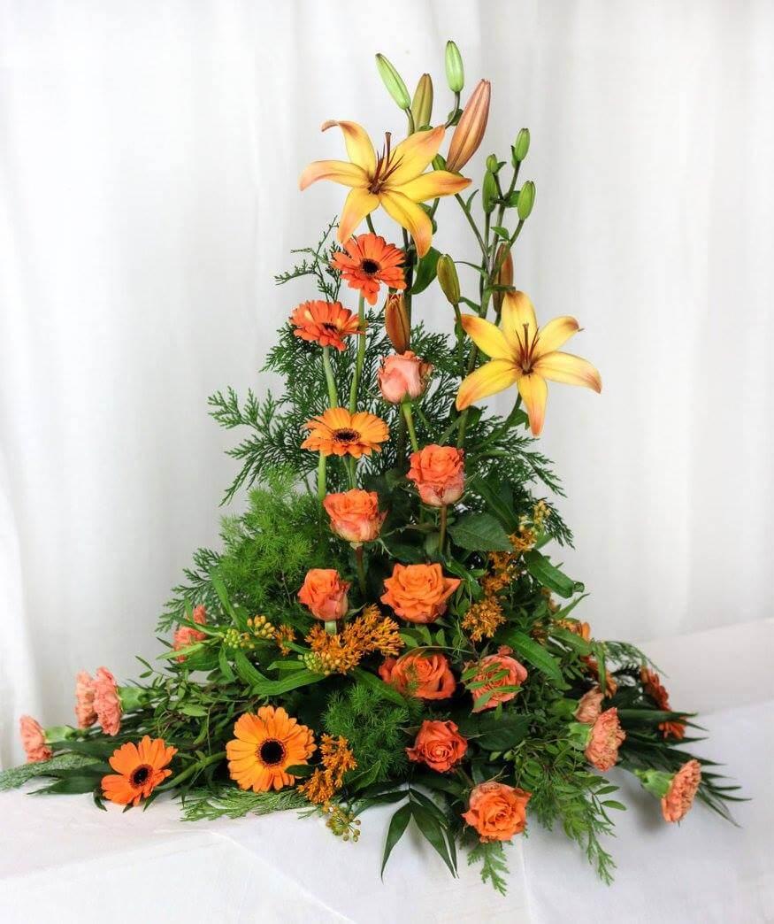 Hög sorgdekoration i varma orangea nyanser. Blomvalet varierar efter säsong men just här har vi använt liljor, germini, rosor, nejlikor och asclepia.