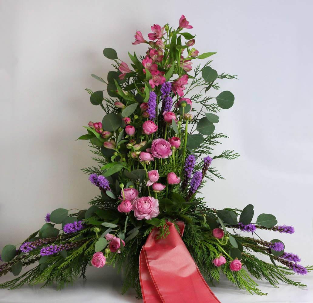Stående sorgdekoration i olika rosa och lila nyanser. Blommorna kan variera efter säsong.