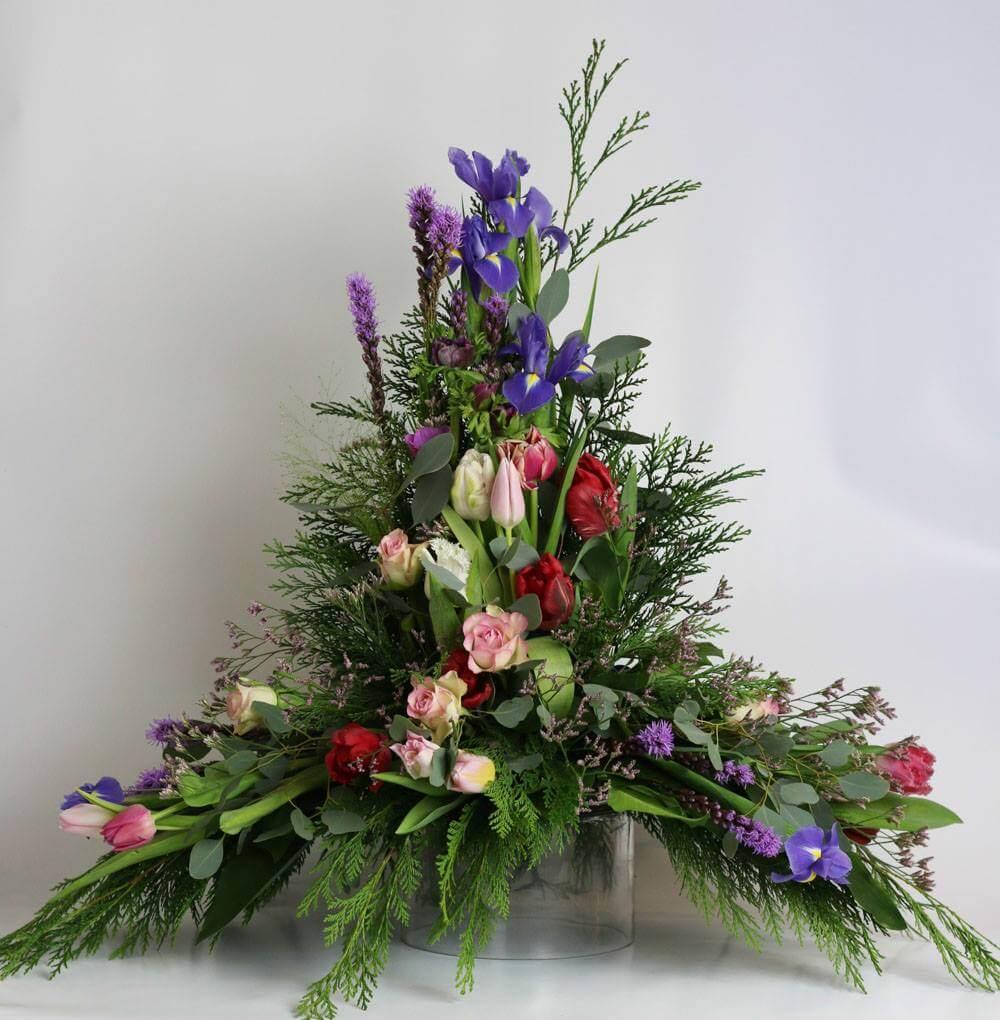 Hög sorgdekoration i blandade färger. Blomvalet varierar efter säsong men just här har vi använt blå iris, lila liatris och tulpaner i olika färger.