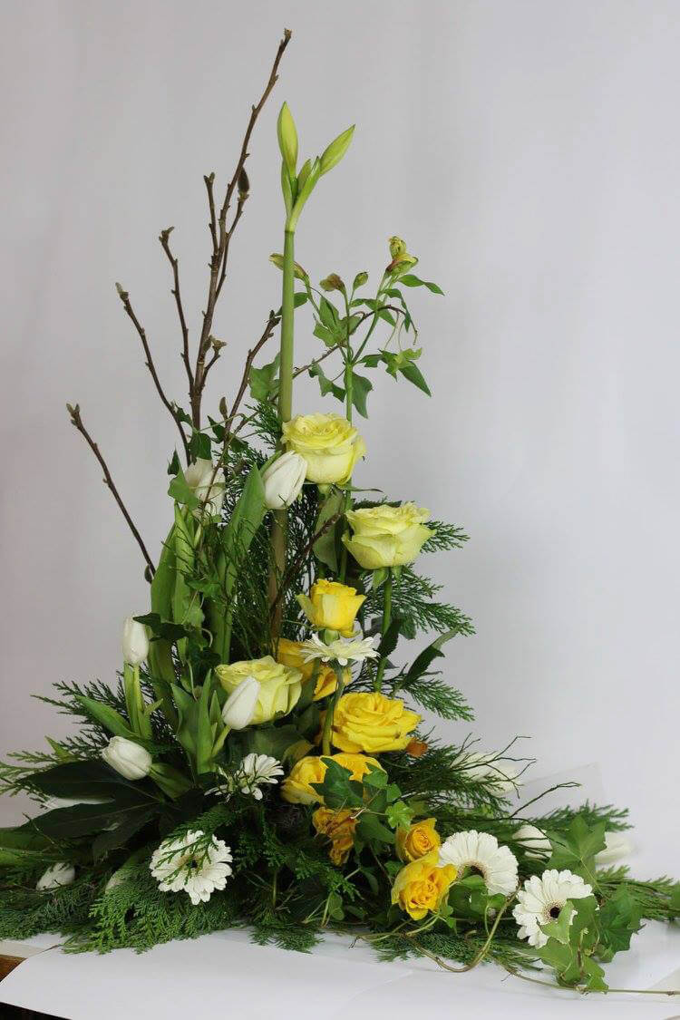 Stående sorgdekoration i olika gula och vita nyanser. Blommorna kan variera efter säsong.