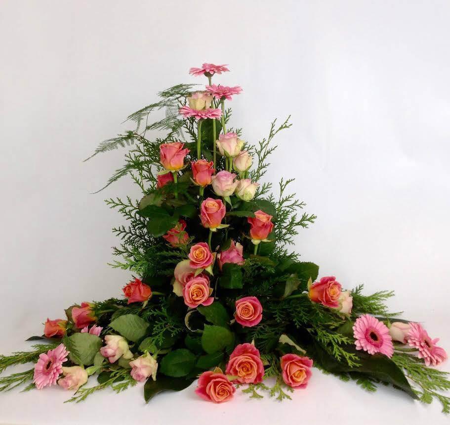 Stående sorgdekoration i olika rosa nyanser. Blommorna kan variera efter säsong.