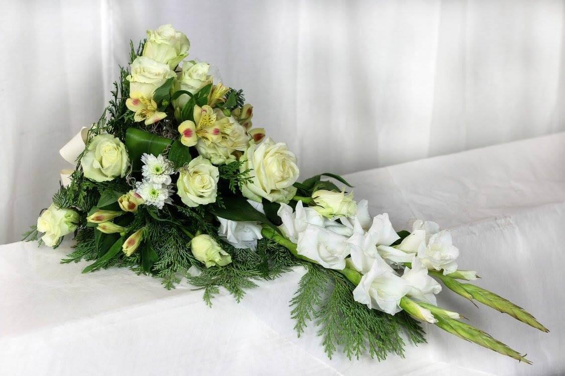 En ljus sorgdekoration i vitt och creme. Blommorna varierar men just här har vi använt rosor, gladiolus, alstroemeria och krysantemum.