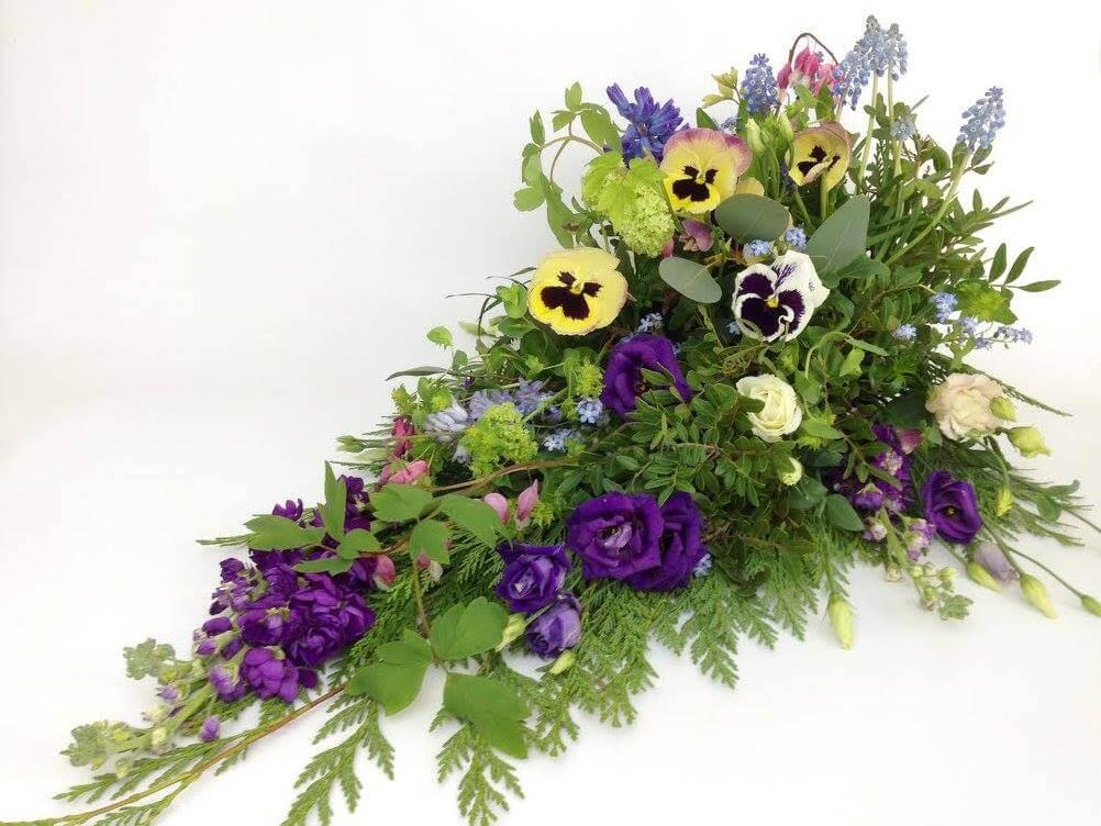 Blå och pastellfärgade vårblommor dominerar denna sorgdekoration. Här har vi använt penséer, pärllhyacinter, lövkoja mm. Blommorna varierar, och detta är en dekoration som är starkt knuten till våren.