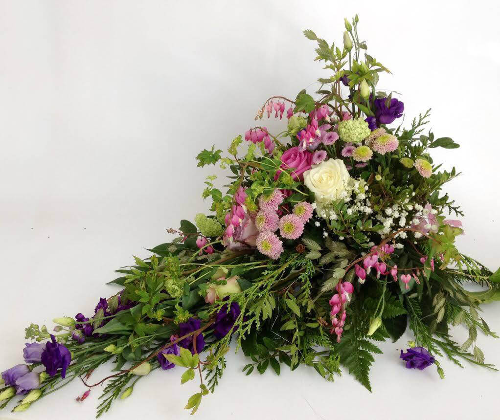 Liggande sorgdekoration i vitt, lila och rosa. Blommorna kan variera efter säsong, men här är det en somrig och lite vildvuxen känsla som dominerar.