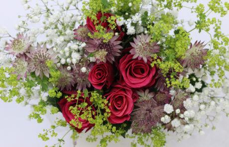 Sommarbukett med rosor, brudslöja, stjärnflocka och daggkåpa.