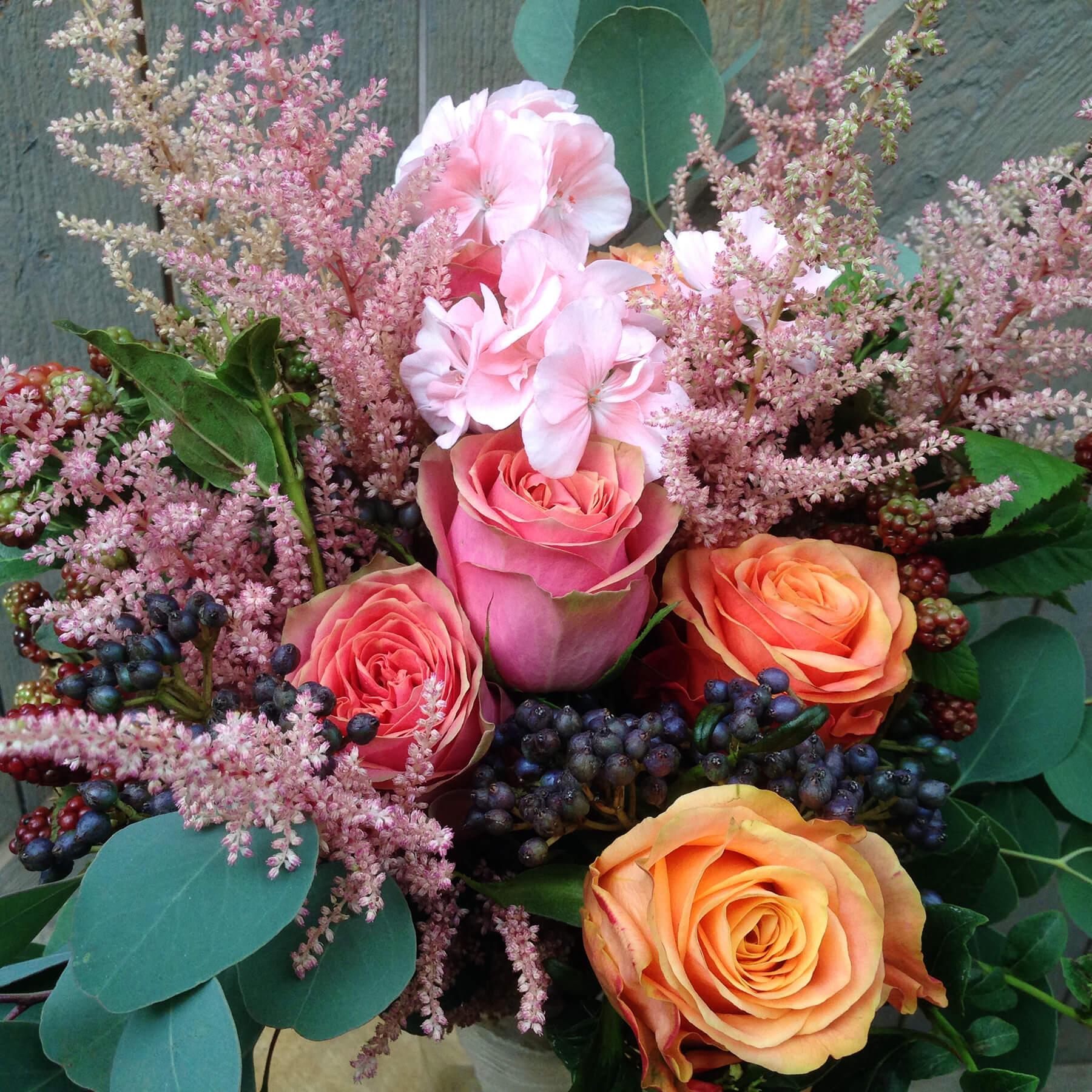 Brudbukett i vild och yvig stil med inslag av trädgårdsväxter som pelargon, astilbe, björnbär och viburnum. Rosa och aprikos nyanser blandas med mörkblått och grönt.