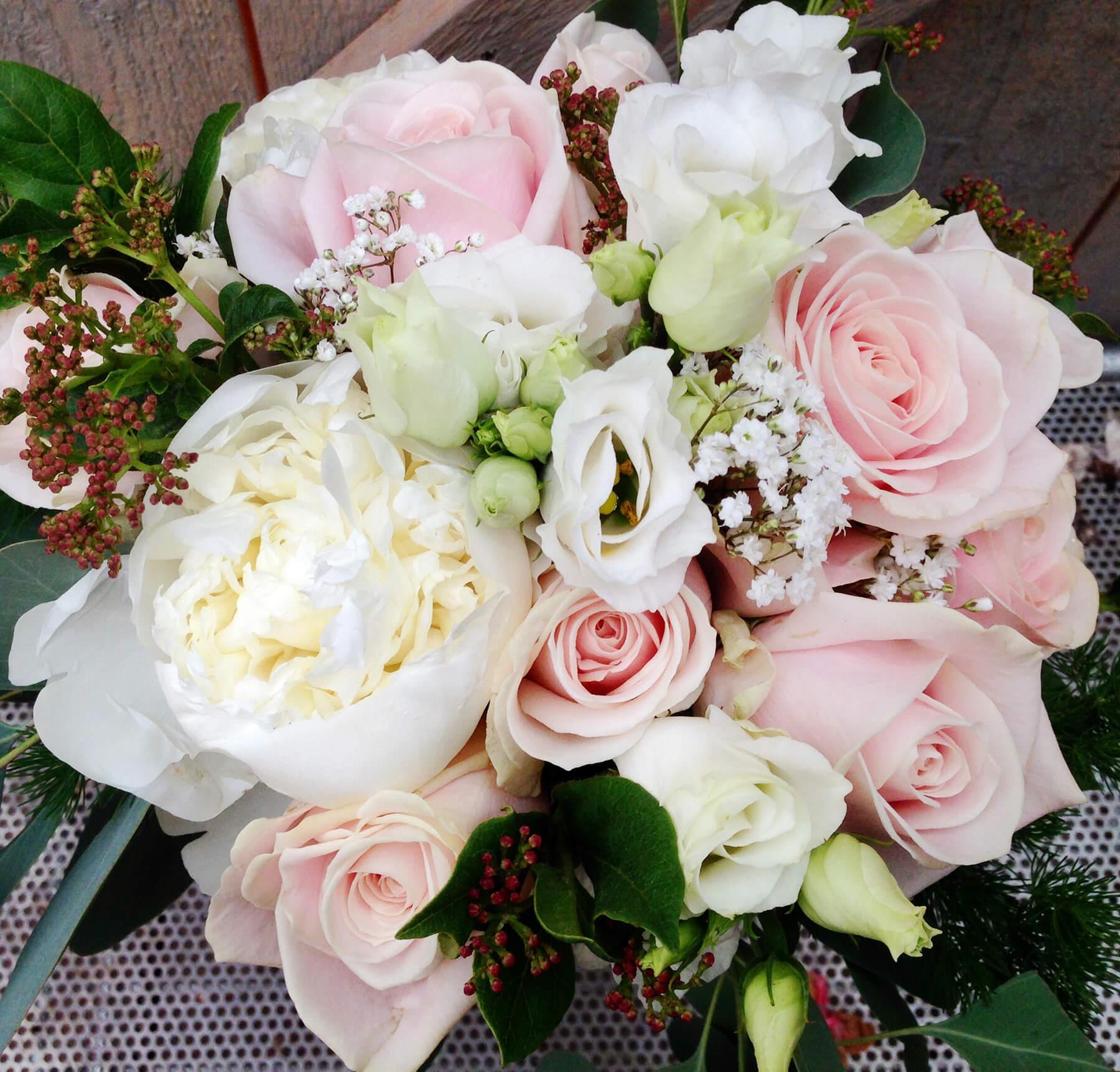 Rundbunden bukett i blekt rosa och vitt. Floristen har använt sig av pioner, rosor, prärieklocka, brudslöja mm.