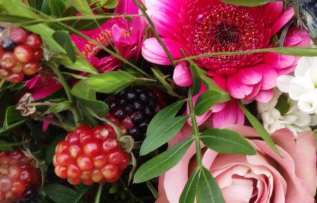 Närbild på bukett i rosa och cerise. Det är rosor, germini, hypericum och björnbär som tillsammans gör den fina helheten.