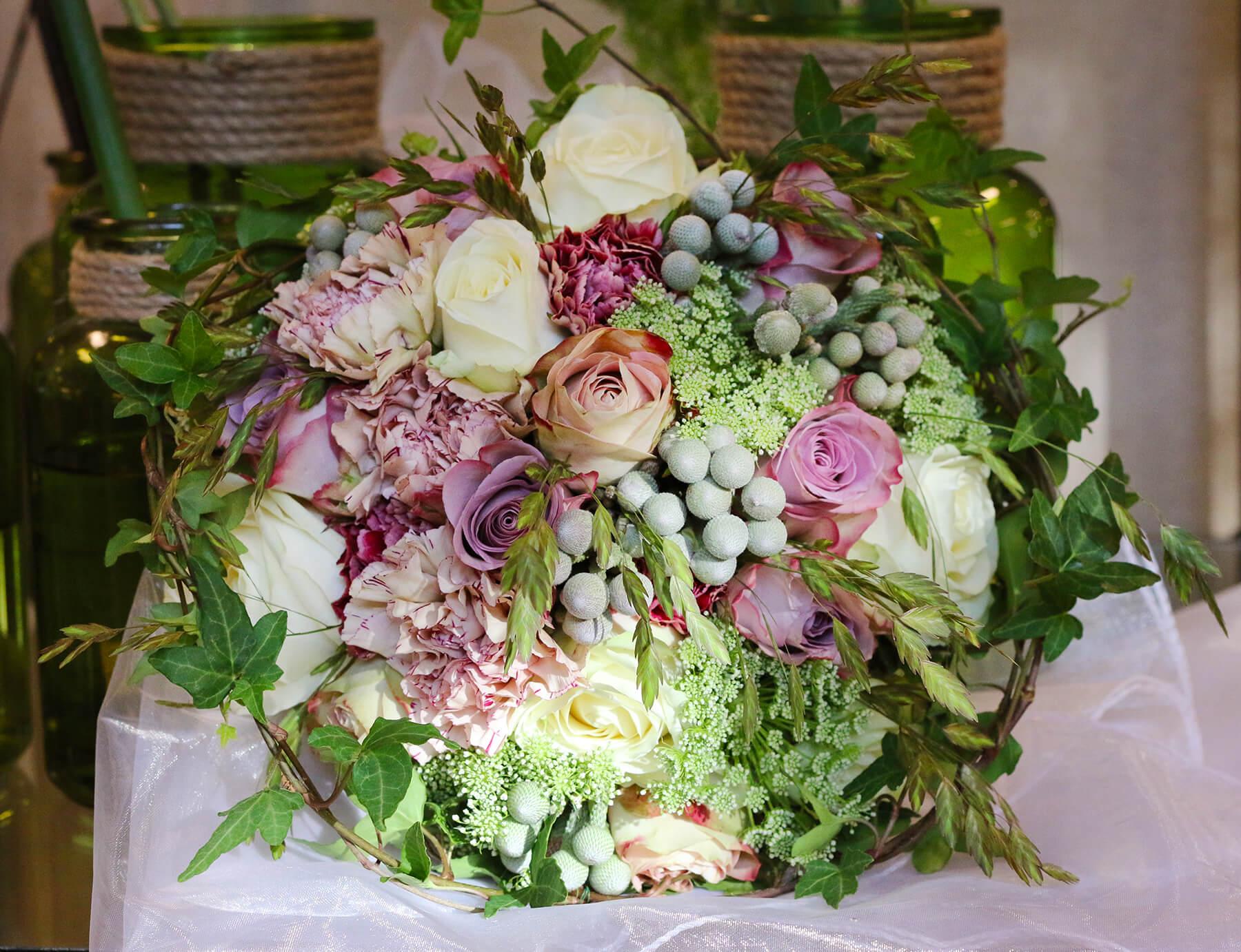 Brudbukett i vitt och dova ljuslila nyanser. Ett bröllop med ganska dämpade färger och vackra nyanser. Vi har använt dessa blommor: Rosor, brunia, nejlikor, ammi majus och grönt.