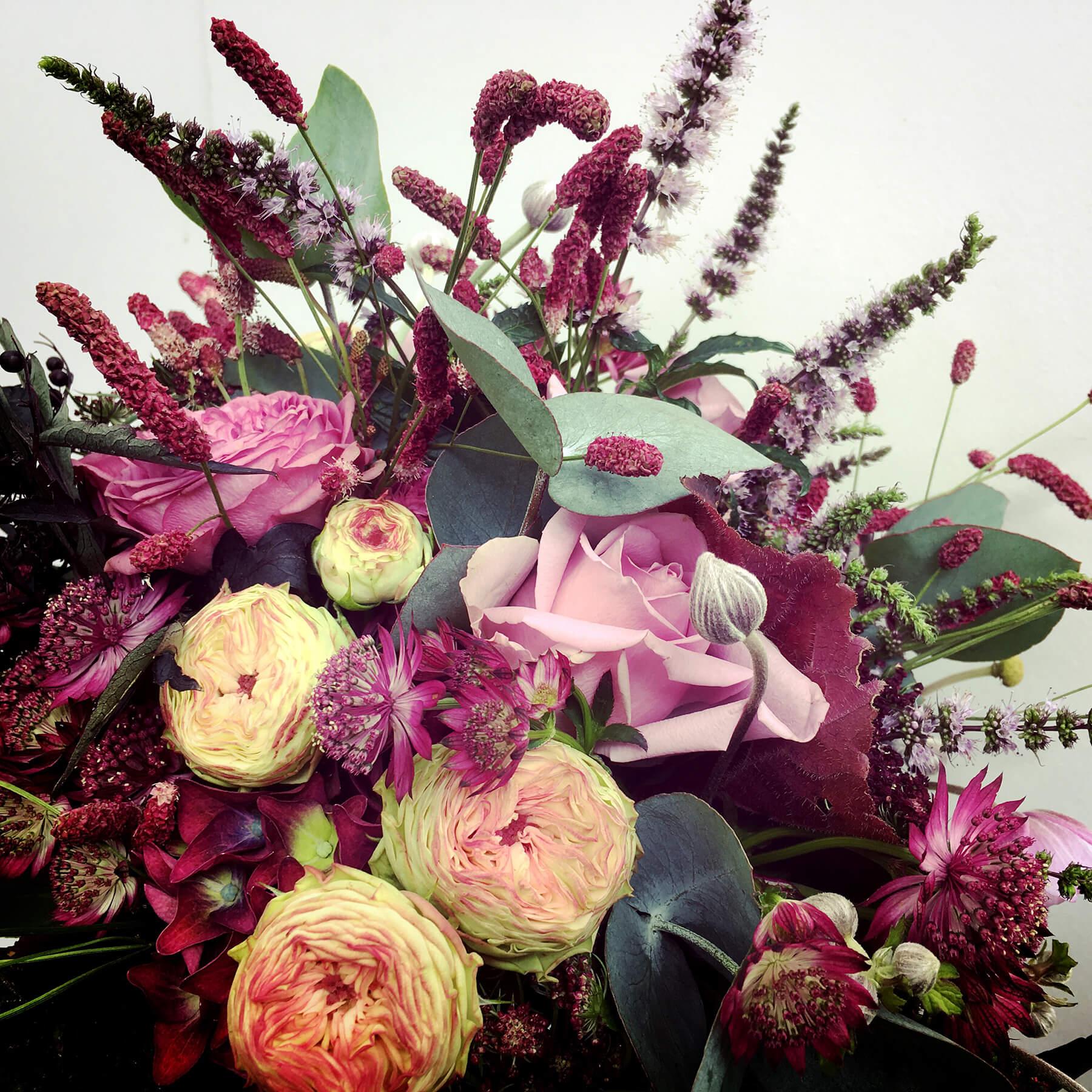 Brudbukett i vinrött, gammelrosa och silvergrönt. Rosor, blodtopp, stjärnflocka och eucalyptus bildar en vacker enhet.