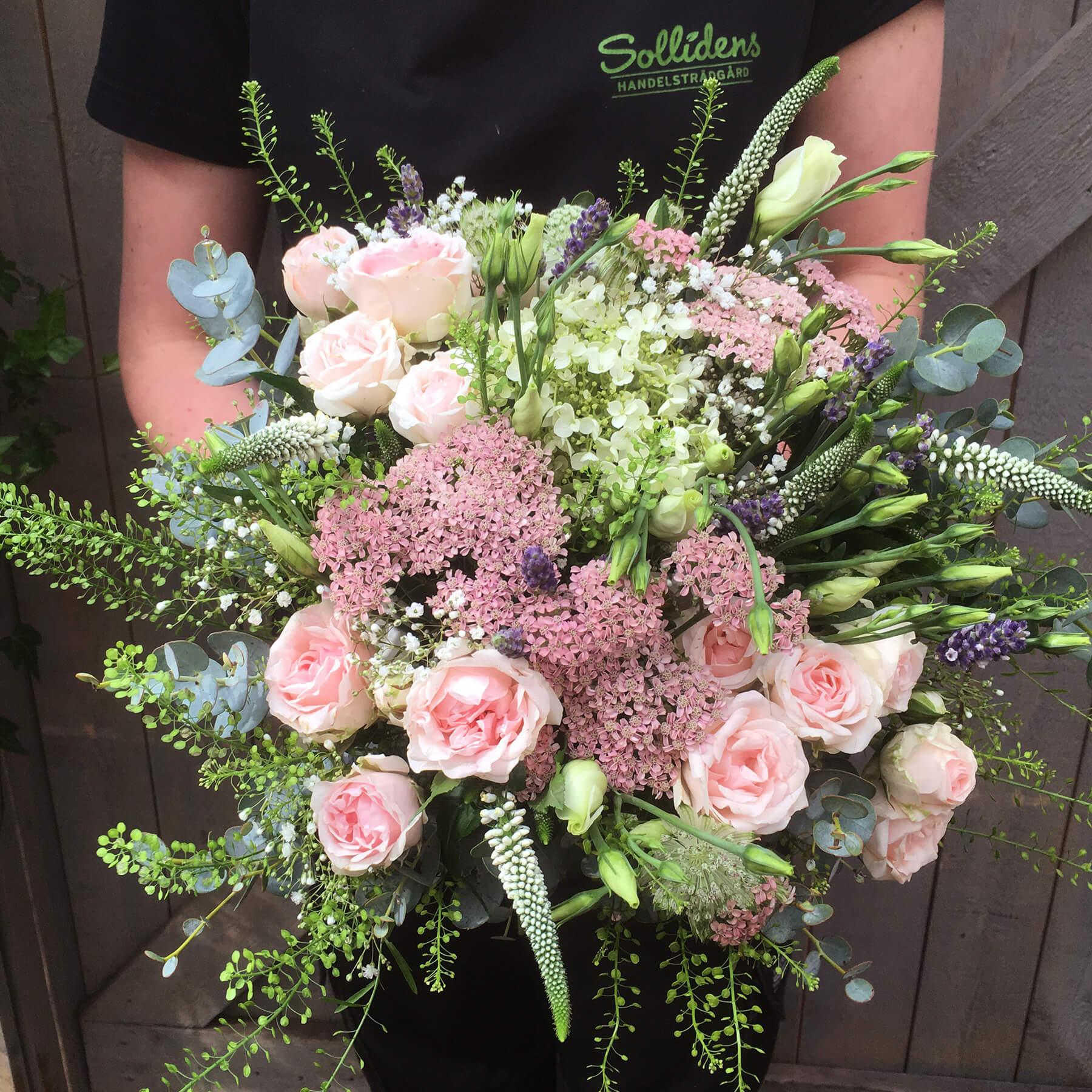 Bukett i vild och yvig stil. Ljusa rosa nyanser blandas med vitt, blått och grönt.
