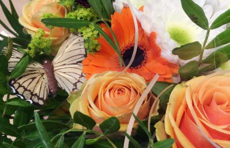 Presentbukett i aprikos, orange och vitt. En liten fjäril kompletterar blommorna.