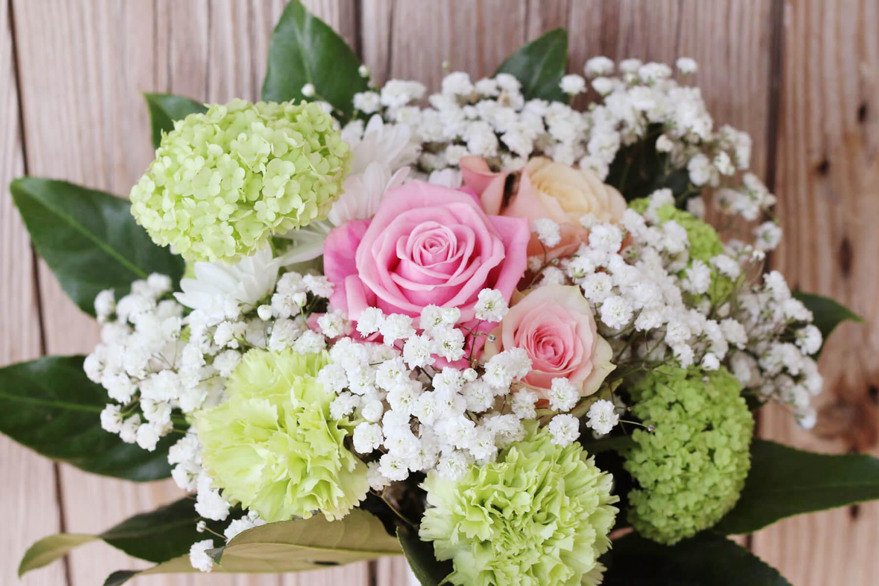 En romantisk bukett i pastellfärger. Floristen har använt sig av rosa rosor i olika nyanser, limegröna nejlikor och olvon samt vit brudslöja.