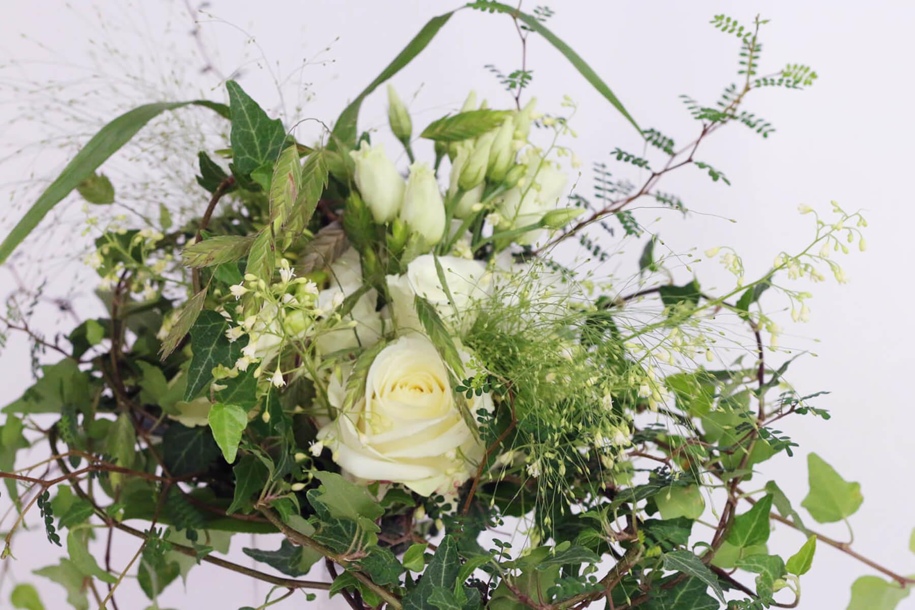 En vild och spretig bukett i bohemisk stil. Färgskalan är enkel, bara vitt och grönt. Floristen har använt sig av rosor, prärieklocka, murgröna, fontängräs, dvärgkowhai mm.