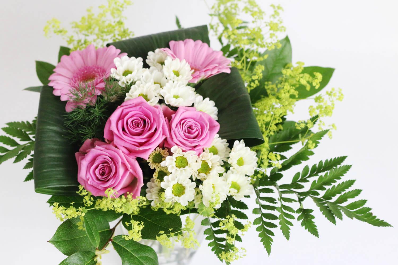 Somrig bukett i rosa och vitt, med rosor, santini, germini, daggkåpa och grönt.