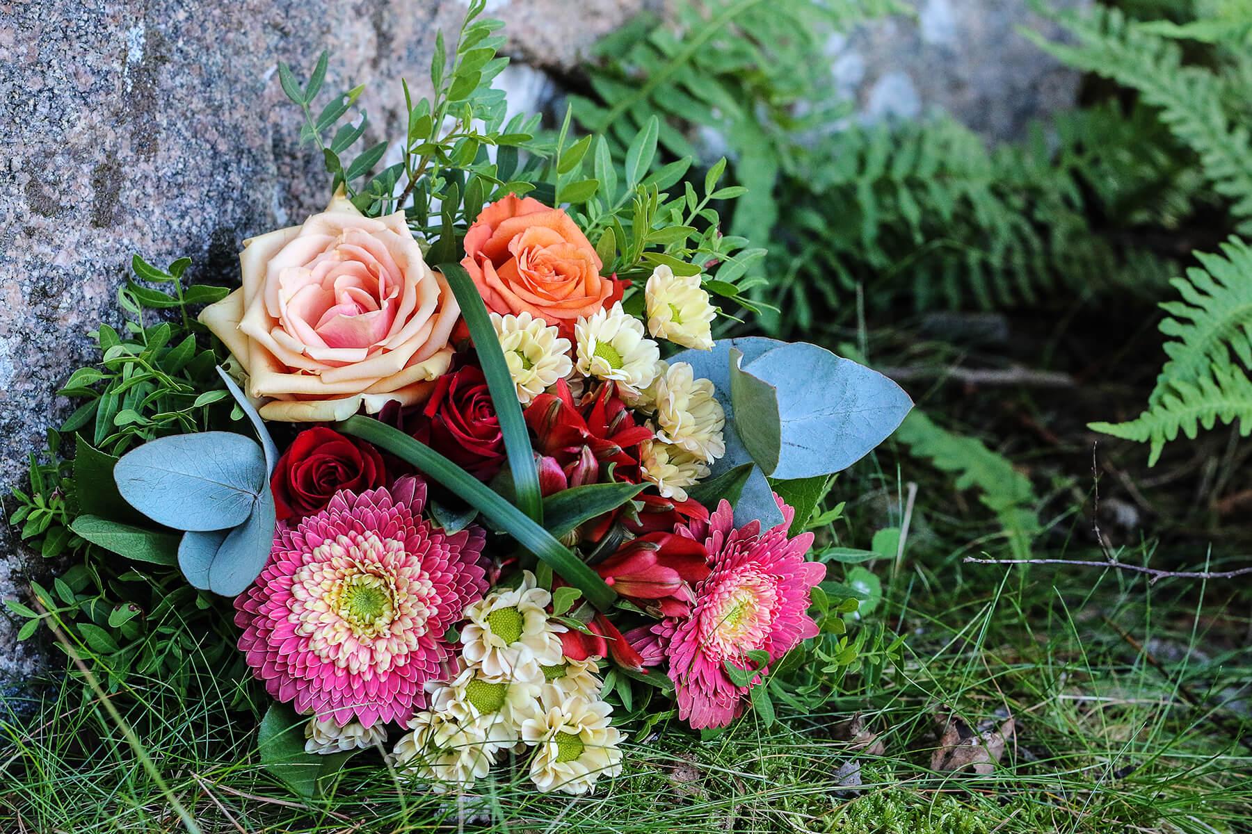 Bukett vid graven. Blommorna går i rosa, rött och aprikos.