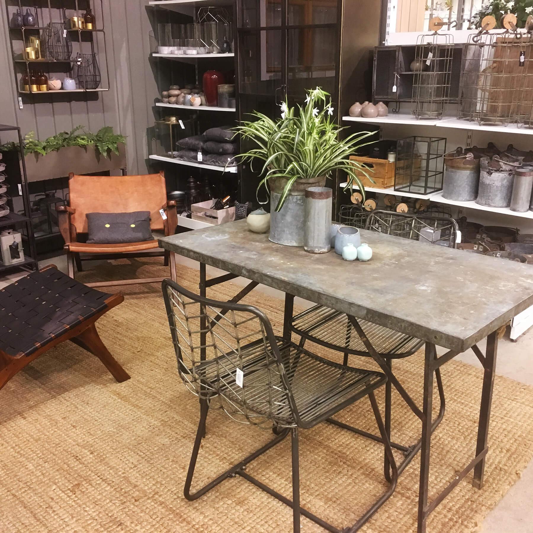 Del av interiöravdelningen på Sollidens handelsträdgård. Fåtöljer i trä och skinn kombineras med bord, stolar och vaser i rå metall.