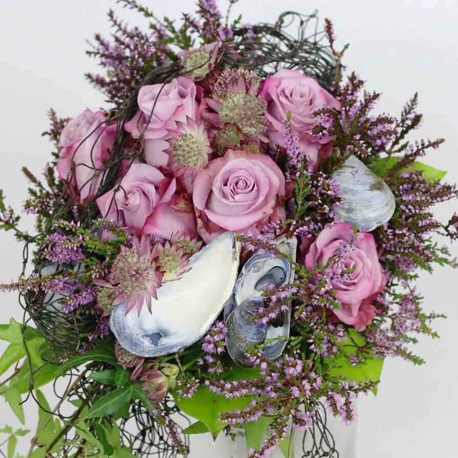 Blommor till bröllop: Brudbukett med ljuslila rosor, ljung och blåmusslor. Lite fisknät hänger ner tillsammans med murgrönan. Passar till ett bröllop i Sotenäs kommun på västkusten!